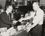 John Patterson speaking with the man behind the counter in a general store.
