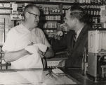 John Patterson speaking with a man behind the counter in a general store.