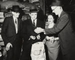 Governor John Patterson with his wife and two men, examining Bob's B-Square hog feed.