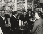 John Patterson with his wife and three men, having drinks in drug store.