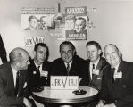 Lyndon Johnson seated at a table with four other men, surrounded by Kennedy-Johnson campaign signs.
