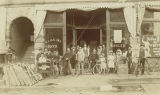 Group of men and children with bicycles in front of the B. J. Malone grocery store, probably in...