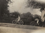 Ellen Hildreth and one of her brothers riding bicycles down a sidewalk, probably in Albany,...