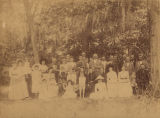 Large group gathered outdoors under moss-covered trees.
